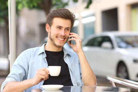 hablando por telefono: Hombre hablando por el teléfono móvil en una tienda de café sentado en la terraza al aire libre y con una taza