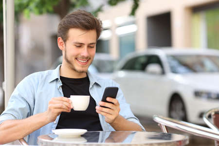 a young man: Man using a smart phone in a coffee shop sitting in the terrace outdoor and holding a cup