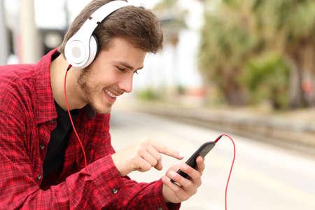 escuchar: Adolescente aprendizaje de los estudiantes con el curso en l�nea en un tel�fono inteligente en un rato estaci�n de tren est� a la espera Foto de archivo
