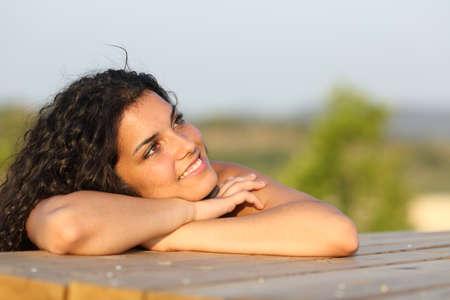 mujer meditando: Chica Candid pensando y mirando hacia los lados de relax en un parque al atardecer con el cielo en el fondo