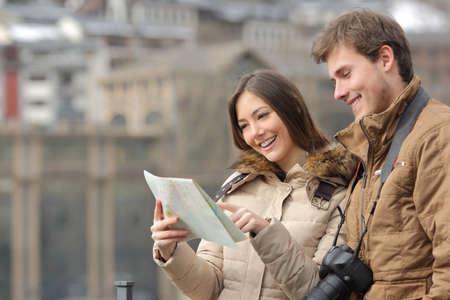 planificación familiar: Pareja de turistas consultoría una guía en invierno con un fondo urbano