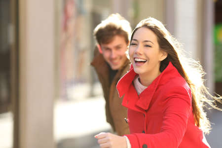 winter fashion: Happy couple running in the street in a sunny day