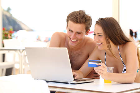 Couple buying online on holidays with a laptop and credit card on the beach