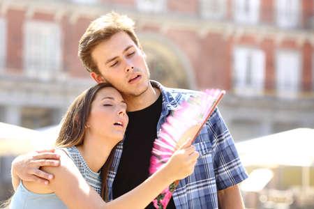 Couple suffering summer heat and fanning with a fan Foto de archivo