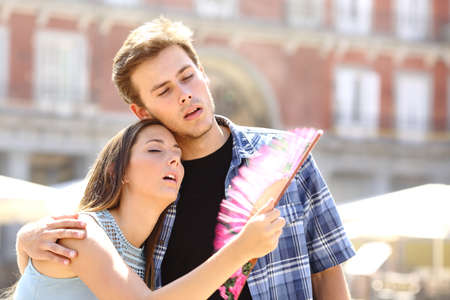 Couple suffering summer heat and fanning with a fan Standard-Bild