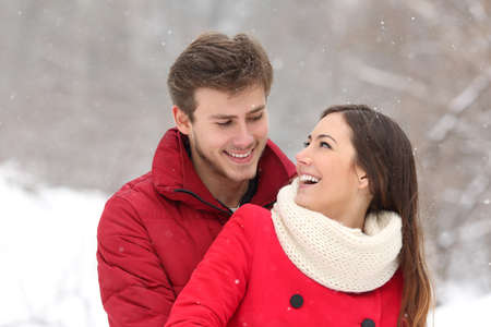 girl portrait: Couple falling in love at first sight in winter outdoors while snowing