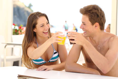 laughing girl: Friends toasting in summer vacation in a restaurant terrace on the beach Stock Photo