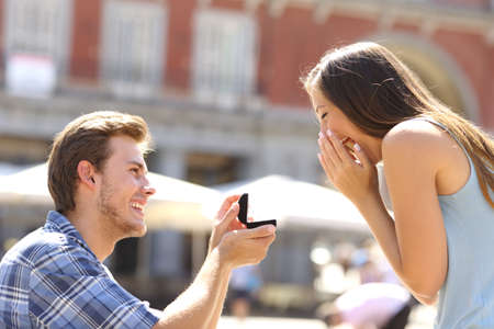 diamond jewelry: Proposal in the street with a man asking marry to his happy girlfriend
