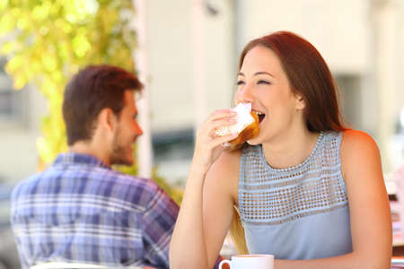 funny people: Happy woman eating a cupcake in a coffee shop terrace Stock Photo