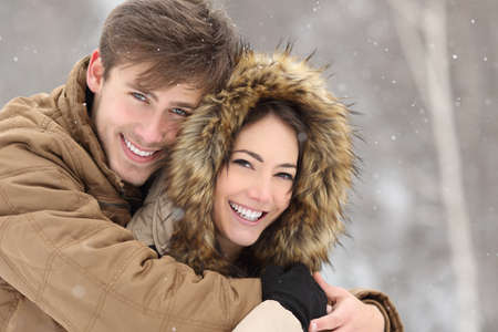 Couple laughing with a perfect smile and white teeth and looking at camera in winter holidays Foto de archivo