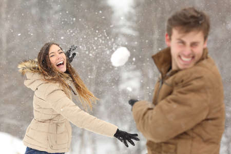 snow falling: Couple playing with snow and girlfriend throwing a ball in winter holidays
