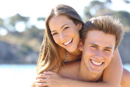 Šťastný pár s dokonalým úsměvem a bílé zuby představují na pláži při pohledu na fotoaparát