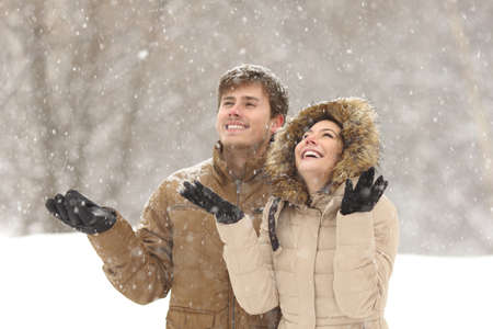 snow woman: Funny couple watching snow in winter during a snowfall on holidays Stock Photo