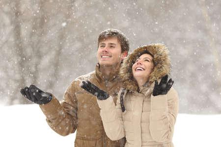 Lustige Paare, die im Winter Schnee während Schneefälle in den Ferien