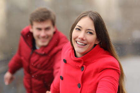 Happy couple wearing red jackets running towards camera in winter