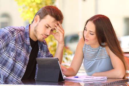aprendizaje: Dos preocupados frustrado estudiante estudiar y aprender con un amigo enseñándole y el uso de una tableta