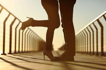 hombre cayendo: Luz posterior de un par de abrazos piernas silueta con amor en un puente al atardecer Foto de archivo