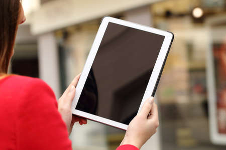 Woman using and showing a blank tablet screen in the street in front a store Foto de archivo