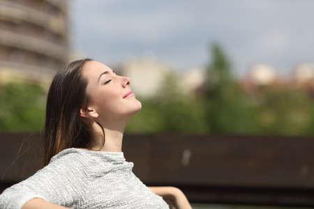 Miejskie kobieta siedzi na ławce w parku i oddychając głęboko świeżym powietrzem Zdjęcie Seryjne