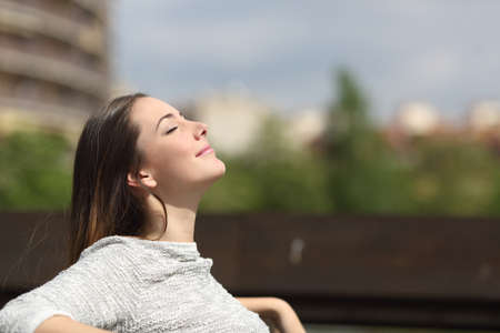 meditation woman: Urban woman sitting on a bench of a park and breathing deep fresh air Stock Photo