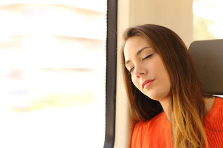public transportation: Passenger woman sitting and sleeping inside a train during a travel Stock Photo