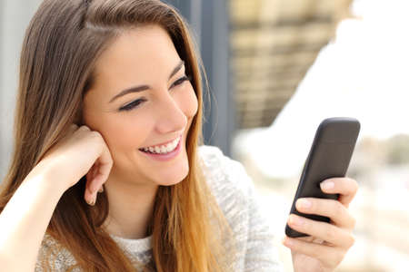 幸せな女のメディアやモバイルのスマート フォンでテキスト メッセージの閲覧