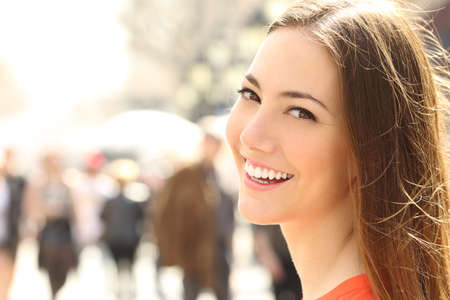 smile close up: Woman face smile with perfect teeth and smooth skin looking you on the street Stock Photo