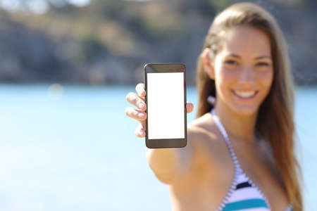 Sunbather woman wearing bikini showing blank phone screen on the beach in summer vacations Stock Photo