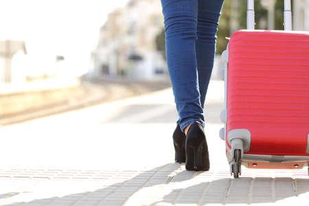 valise voyage: Jambes de femme de voyageurs à pied avec des bagages dans une gare alors qu'elle est en attente