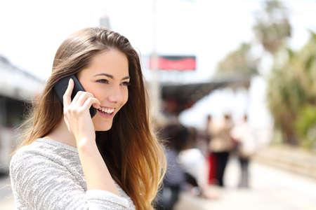 llamando: Mujer que habla en el teléfono teniendo una conversación mientras se espera en una estación de tren