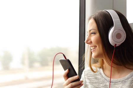 Gelukkige tiener passagiers luisteren naar de muziek reizen in een trein en kijkt door het raam