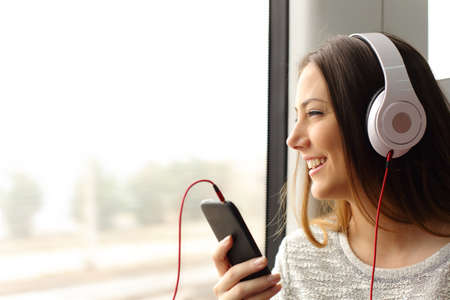 listening device: Happy teen passenger listening to the music traveling in a train and looking through the window