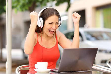붉은 셔츠를 입고 커피 숍에서 노트북을보고 기쁘게 우승자 소녀 스톡 콘텐츠