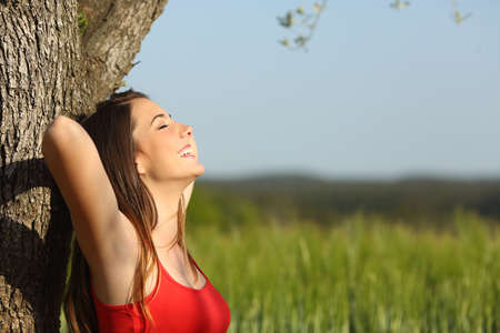 Woman resting and relaxed comfortable leaning in a tree in a meadow in summertime