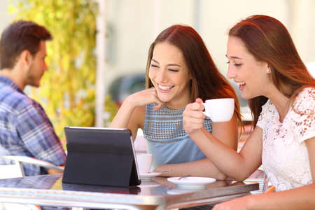 videos: Two friends or sisters watching videos in a tablet in a coffee shop terrace