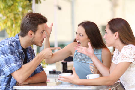 aggressive people: Discussion of three angry friends arguing in a coffee shop Stock Photo
