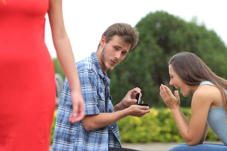 cheater: Cheater man cheating during a marriage proposal with his innocent girlfriend Stock Photo