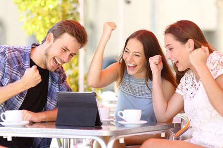 ganador: Amigos ganador euf�ricos utilizando una tableta en una terraza cafeter�a Foto de archivo