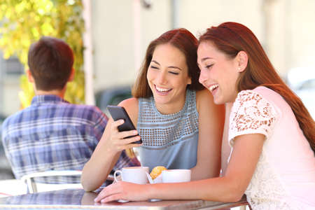 women coffee: Two happy friends or sisters sharing a smart phone in a coffee shop terrace looking at device in summer