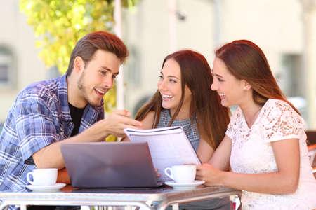 aprendizaje: Tres estudiantes que estudian y que aprenden en una cafetería con un ordenador portátil y notas