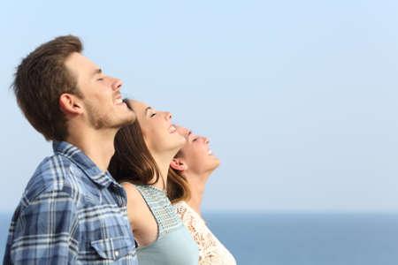 Groep van drie vrienden ademen diep de frisse lucht op het strand