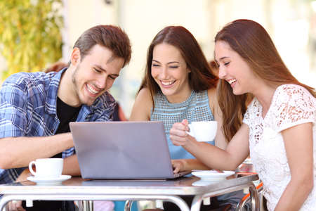 three friends: Three happy friends watching videos in a laptop in a coffee shop terrace Stock Photo