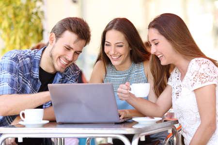 riendo: Tres amigos felices viendo v�deos en un ordenador port�til en una terraza en la cafeter�a