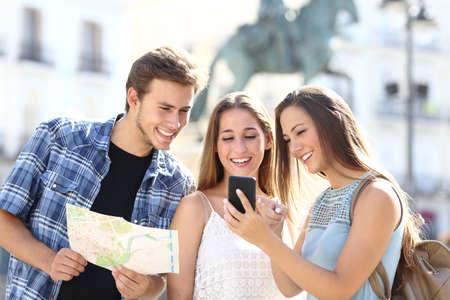 Drie toeristische vrienden overleg met gps op smart phone in een toeristische plaats met een monument op de achtergrond Stockfoto