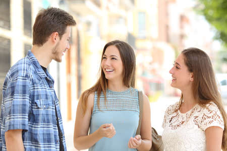 Three happy friends talking taking a conversation on the street in a sunny day with buildings in the background