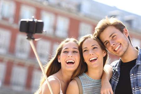 hombre disparando: Grupo de tres amigos turistas que toman selfie con la mano teléfono inteligente mantenga monopie en la calle