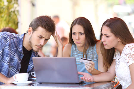 Three shopper friends buying online with credit card finance problems in a coffee shop