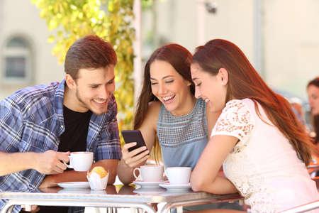 with friends: Tres amigos felices viendo los medios sociales en un tel�fono inteligente en una cafeter�a