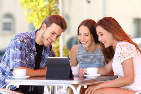 viendo television: Tres amigos felices viendo la televisi�n o los medios de comunicaci�n social en una tableta en una terraza cafeter�a