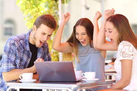 sorprendido: Amigos felices que dan un regalo portátil a una niña sorprendida en una cafetería Foto de archivo